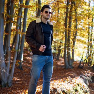 Mann mit schwarzer Bomberjacke im Wald